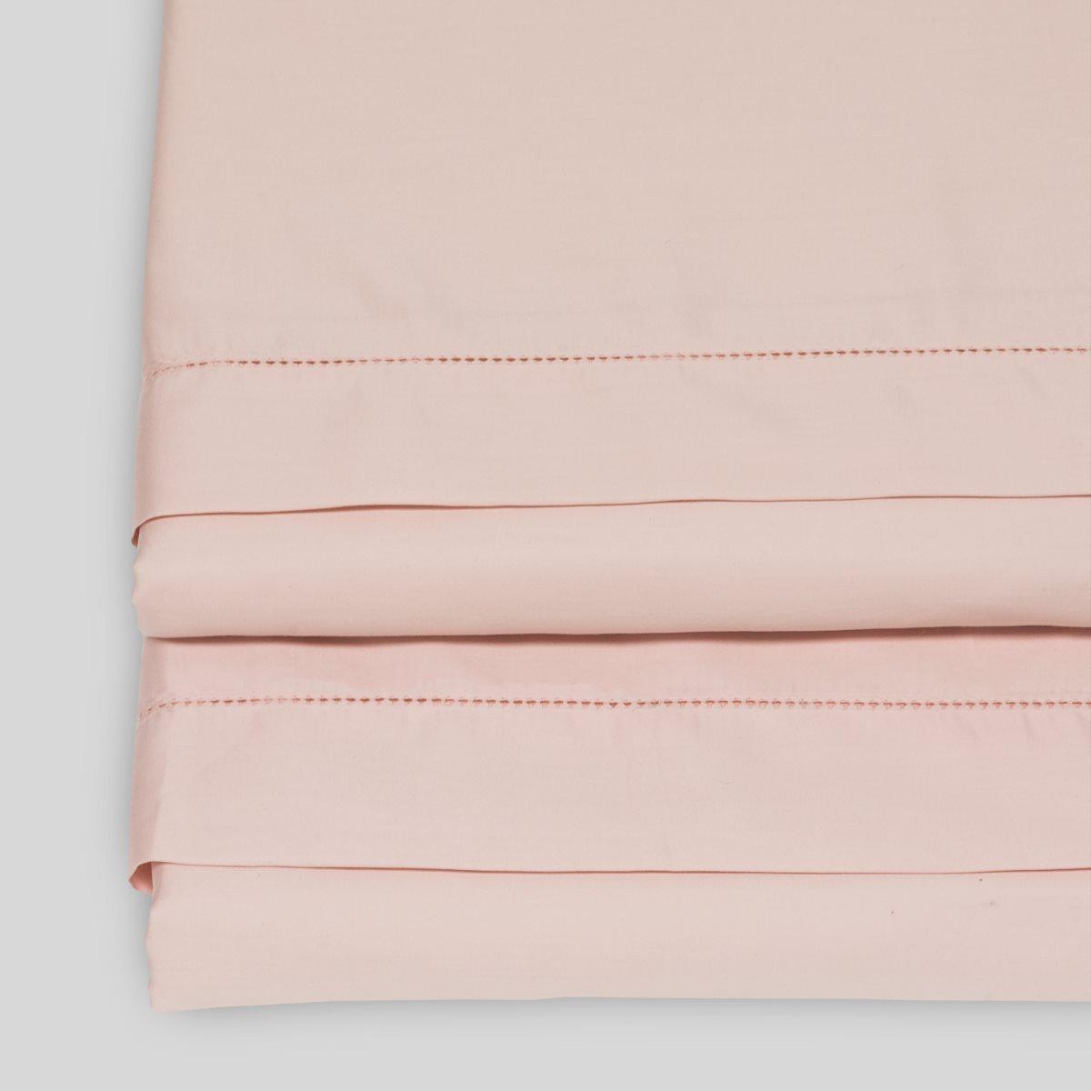 cream flat sheet on floral bedding
